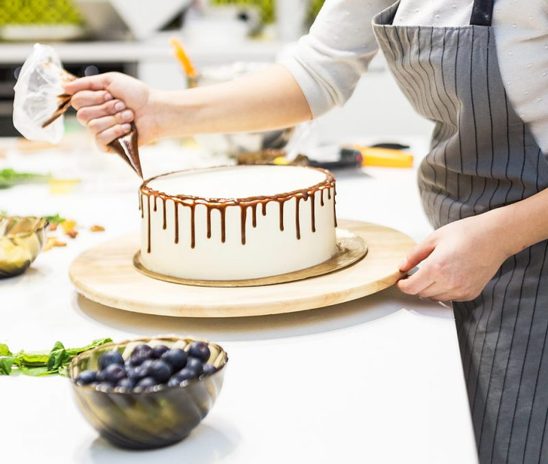 konditor lägger glasyr på tårta